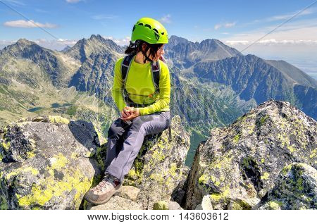 HIGH TATRA SLOVAKIA - AUGUST 20 2015: Tourist in the mountains. Young woman on the top admiring mountain views.