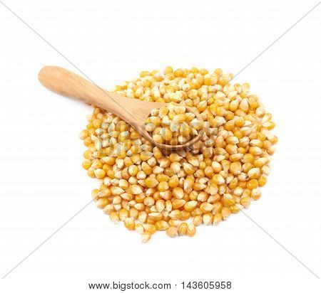 Pile of corn kernels with a serving wooden spoon over it, composition isolated over the white background