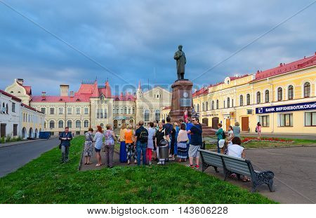 RYBINSK RUSSIA - JULY 21 2016: Unidentified tourists listen to story of guide on Red Square near monument to Lenin and building of former Grain Exchange Rybinsk Russia
