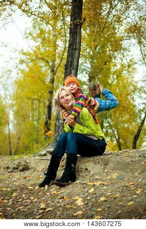 young mother and her son outdoor in the autumn park