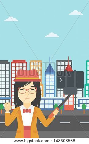 An asian woman making selfie with a selfie-stick. An asian woman taking photo with cellphone and waving on a city background. Vector flat design illustration. Vertical layout.