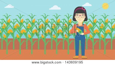 An asian female farmer holding a corn cob. Young farmer standing on the background of corn field. Vector flat design illustration. Horizontal layout.