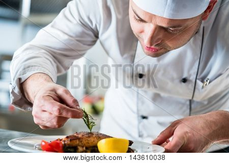 Chef garnishing the food on plate to complete the dish in restaurant kitchen