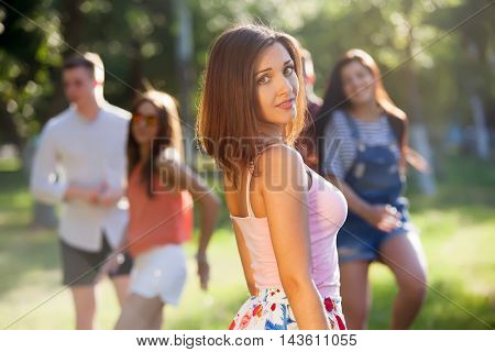 summer holidays and teenage concept - young girl out with friends outside. Portrait of a young girl and his friends in the background.