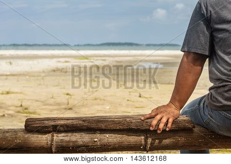 Rayong, Thailand - August 06, 2016: Unidentified Hand Body Part Of A Man Sitting On Wooden Near The Sea.