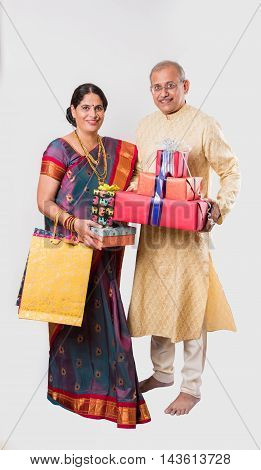 portrait of senior indian Couple in traditional clothing standing with gift boxes and shopping bags, isolated over white background