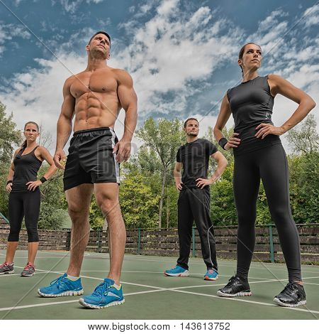 Fitness team of four athletes posing, square imare