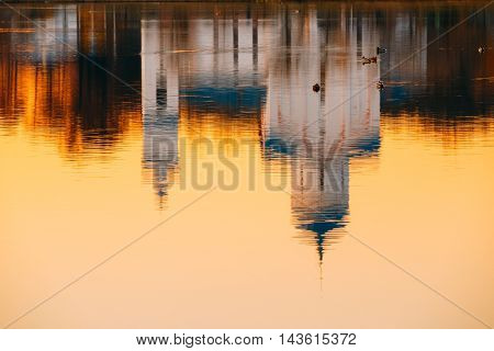 The Reflection Image Of Russian Orthodox Christian Temple Church Chapel On Sunset Sunrise Dawn River Lake Water Surface, Russia. A Small Flock Of Floating Ducks Back From.