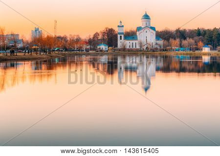 The View Of Alexander Nevsky Orthodox Christian Church With Bell Tower Built On The Lake Shore In Sunset Sunrise Dawn, Early Spring, Gomel, Homiel, Belarus