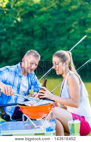 Man and woman having barbeque grilling the fish they caught sport fishing