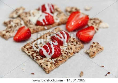 Red Fresh Strawberries are on the Cracker with Grains,Condensed Milk  on the White Paper.Breakfast Organic Tasty Food.Cooking Vitamins Ingredients.Summer Fruits.Selective Focus