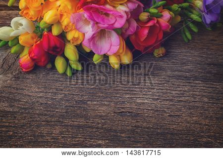 Fresh freesia flowers on wooden table background with copy space, retro toned