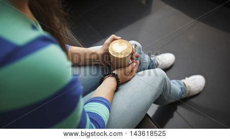 The cup with coffee in woman's hands and shape of heart is painted in coffee