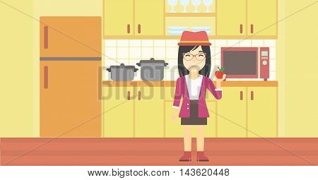 An asian young woman holding an apple in the kitchen. Young woman eating an apple in the kitchen. Woman with an apple at home. Vector flat design illustration. Horizontal layout.