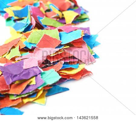 Pile of multiple colorful torn paper pieces isolated over the white background, close-up crop composition with a shallow depth of field