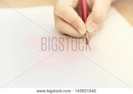 Child is drawing red heart by pencil