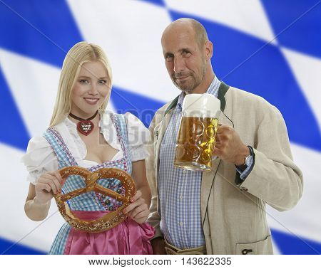 Bavarian Oktoberfest Couple with beer mug and pretzel with a bavarian flag in the background