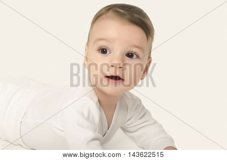 Cute baby boy looking surprised. Adorable baby crawling looking curious isolated on white. Baby lying on his tummy.