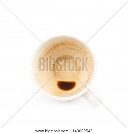 Dirty ceramic cup with a coffee leftovers isolated over the white background, top view above foreshortening