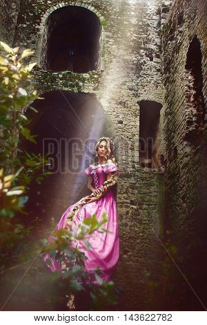 Beautiful young woman with long hair braided in a braid sitting in the window of the tower.