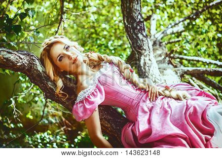 Beautiful young woman with long hair braided in a braid, is a tree.