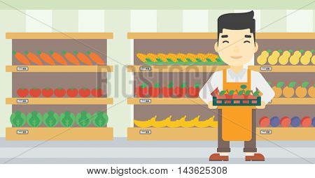 An asian young male supermarket worker holding a box with apples on the background of shelves with vegetables and fruits in supermarket. Vector flat design illustration. Horizontal layout.