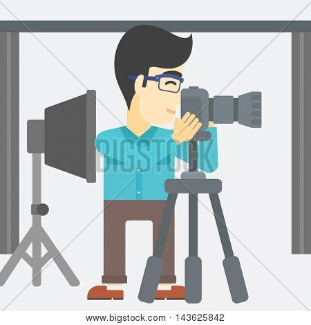 An asian young photographer working with camera on a tripod in photo studio. Man taking photo with professional digital camera in the studio. Vector flat design illustration. Square layout.