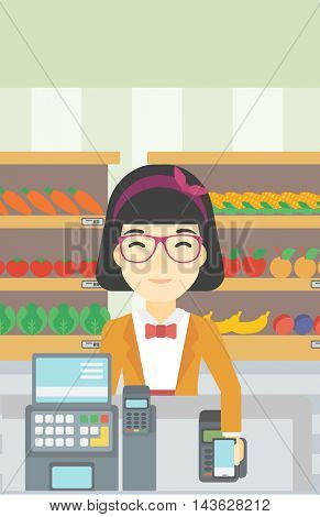 An asian young woman paying wireless with smartphone at the supermarket checkout . Female customer making payment for purchase with smartphone. Vector flat design illustration. Vertical layout.