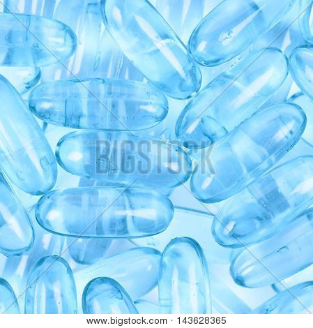 Surface coated with multiple blue softgel pills as an abstract medical background composition