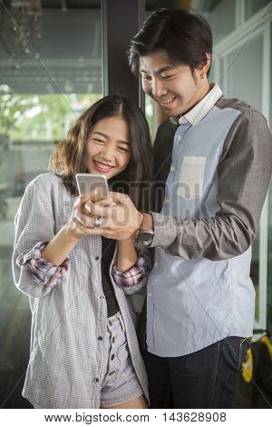 asian younger man and woman watching on smart phone with happy face, internet and social media concept