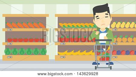 An asian thoughtful man standing at the supermarket with supermarket trolley full with products and holding a shopping list in hands. Vector flat design illustration. Horizontal layout.