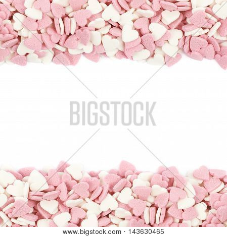 Copyspace composition with the borders made of heart shaped sugar sprinkles isolated over the white background