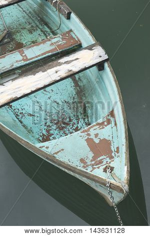 Old blue wooden boat on the lake near the shore.