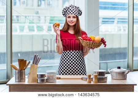 Young cook with fruits in the kitchen