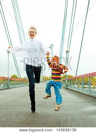 happy young mother and her son running and jumping outdoor on the bridge