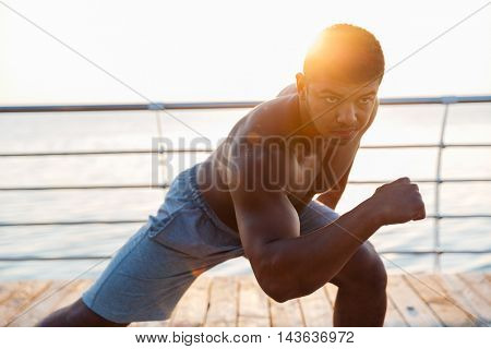 Attractive muscular african american young man athlete warming up and doing exercises on pier