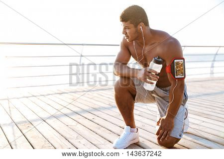 Handsome african american young man athlete listening to music from blank screen mobile phone in armband