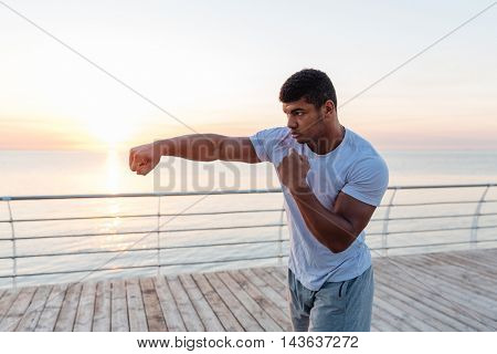 Handsome african american young man athlete boxing outdoors on sunrise