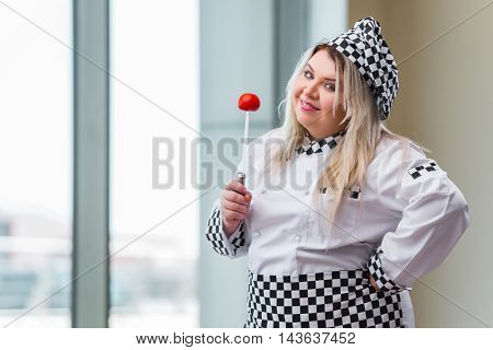 Woman chef cutting tomato at the kitchen