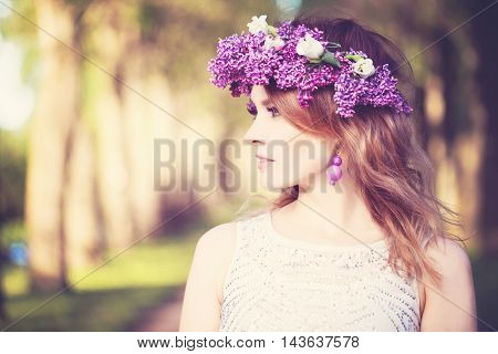 Beautiful Woman Outdoors. Beauty Summer Girl with Flowers Wreath on Sunny Greenery Background