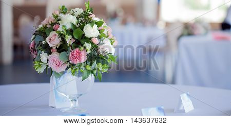 Wedding floristry. Beautiful lush bouquet on the table in the restaurant