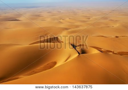 Aerial view on the beautiful landscape of the Namib Desert at sunset. Flying on a small plane over the desert is one of the most popular tourist attractions in Namibia