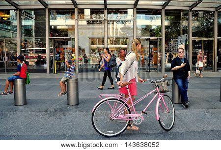 New York City - August 4 2013: Woman wheeling her pink bicycle past the front entrance to the Time Warner Center at Ten Columbus Circle