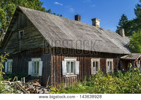 Old rustic abandoned wooden house with white windows and eternit roofed with smoking chimneys