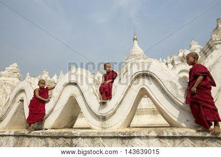 AsianBurma Three Novices monks on the Hsinbyume Pagoda sky mandalayMyanmar