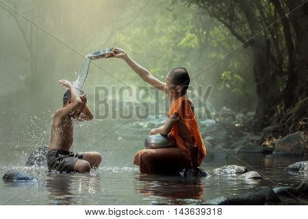 Novice monk playing water splash with the boy on the brook