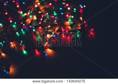 Christmas lights on dark background. Decorative garland. Tinted photo.