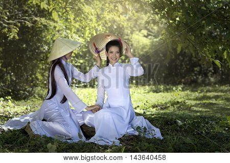 Two women in Ao Dai vietnam traditional dress under tree