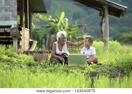 Grandmother and grandson with laptop on the field