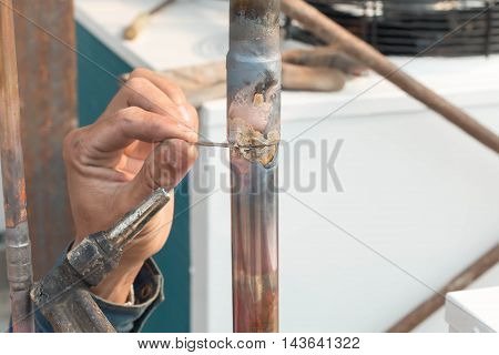 Plumbing contractor works sweating the joints on the copper pipe domestic water system on a luxury custom home